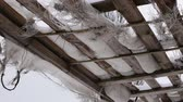 old roof of boards and torn fabric. a strong wind is blowing and threads are hanging. winter