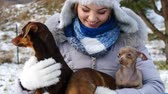 собака : Woman playing with her little dogs outside winter