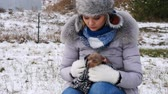 ушки : Worried woman taking care of small dog during winter
