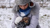 беспокоиться : Worried woman taking care of small dog during winter