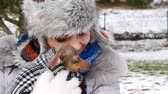 Woman playing with her little dog outside winter