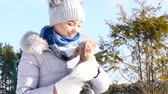 miniatura : Woman playing with her little dog outside winter