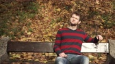 cardigan sweater : Man sitting on bench in autumnal park 4K