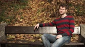 Man sitting on bench in autumnal park 4K