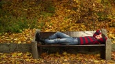 bezdomny : Man lying on bench in autumnal park 4K