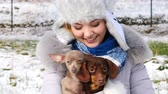 duas pessoas : Woman playing with her little dogs outside winter
