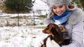 bassê : Woman playing with dachshund during winter