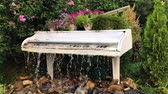 White grand piano water fountain in the summer garden