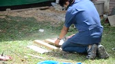 pilar : Man use cutting machine cut quarry tile at garden August 29, 2015 in Phrae, Thailand