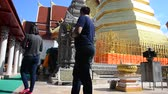 respeito : Asian thai people respect pray and travel and posing take photo at gold chedi of Wat Phra That Cho Hae temple in Phrae, Thailand