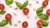 Cherry tomatoes, cheese and fresh green Basil leaves on white background closeup with moving camera on top. Pizza ingredients, pasta. Product concept video footage. Stok Video