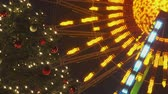 festividades : Decorated Christmas Tree At Night With Illuminated Ferris Wheel Spinning And Blinking In The Background In Slow Motion Stock Footage