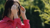 dressing : Portrait of pretty woman dressing sunglasses in a park Stock Footage