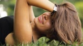 koketní : Attractive woman lying on grass at summertime, she relax and coquettish play with hair.