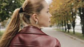requintado : Autumn is coming. Pretty woman in burgundy jacket walk in city street, slowmotion, rear view.