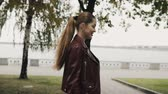 requintado : Autumn is coming. Happy woman in burgundy leather jacket walk in city street, slowmotion.