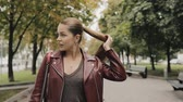 requintado : Autumn is coming. Woman in burgundy jacket walk in city street, slowmotion.