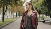 requintado : Autumn is coming. Woman in burgundy leather jacket walk in city street, slowmotion. Stock Footage