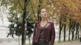 requintado : Autumn is coming. Elegant woman in burgundy leather jacket walk in city street, slowmotion.