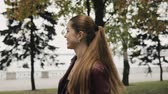 requintado : Autumn is coming. Happy woman in burgundy leather jacket walks in city street, slowmotion. Stock Footage
