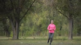 vigoroso : Pretty sportswoman in pink sportswear jogging at forest, healthy lifestyle concept. Slow motion.