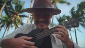 yellow : A young active man with a hat with a mustache in yellow glasses plays on the ukulele among the coconut palms, fools around on camera. Travel Concept