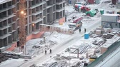 machinery : Winter holidays on construction site in Russia. Stopped cranes and machinery covered with snow. Stock Footage
