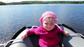 lancha : One small Caucasian girl sitting in motorboat during movement on forest lake. Close up