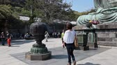 shu : People are photographed against the backdrop of the Great Buddha in Kamakura, Japan Stock Footage