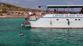 lancha : View from the recreational marine vessel at the blue lagoon with swimming tourists. Sea cruise along the coast. Mediterranean Sea, the village of Latchi, Cyprus Vídeos