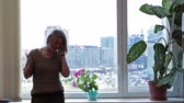 pacing : Woman before huge window with city view through calling on the phone and pacing