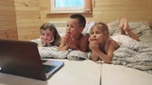 brother : Three children laying in bed before sleeping and watching cartons on laptop