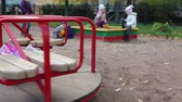 roundabout : Roundabout spinning and children playing in sandbox Stock Footage