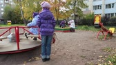 roundabout : Group of children playing on nursery school playgroung with roundabout and sandpit Stock Footage