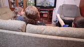 vista : Small brother and sister with mother watching tv in living room