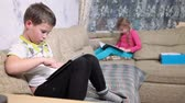 holding : Camera focused on boy using tablet and girl reading the book. Kids sitting on sofa