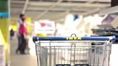 cartn corrugado : SAINT-PETERSBURG, RUSSIA - CIRCA JAN, 2015: Ikea shopping cart stands in showroom with customers walking near. Ikea multinational group is the worlds largest furniture retailer. Russian store Stock Footage