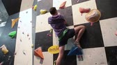 sertlik : SAINT-PETERSBURG, RUSSIA - CIRCA FEB, 2015: Climber climbs the wall and falls down. Rock-climbing championship is in IgelsClub. Sportsmen climb the walls. Igelsclub is a parkour park with climbing gym and trampolines