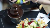 chocolate sauces : Chocolate fountain with fruits plate and human hands with fork dipping orange slices and grapes, close-up
