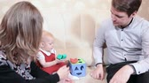 parent : One year baby girl playing on sofa with mother and father. Three people Caucasian family