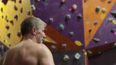 sertlik : Rear view at mature man a climber in front of gym climbing wall, caucasian athlete