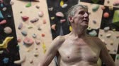 sertlik : Happy and breathing heavily mature climber, standing in climbing gym Stok Video