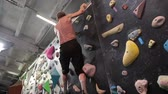 sertlik : Mature man learning the skills of climbing and mountaineering in gym Stok Video