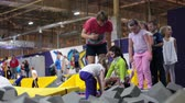 яма : ST. PETERSBURG, RUSSIA - CIRCA OKT, 2015: Children with instructor have fun in pit with foam at trampolines. The Jumping Club 1 is in city mall center Leto Стоковые видеозаписи
