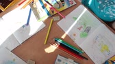 painting : ST. PETERSBURG, RUSSIA - CIRCA MAY, 2015: Boys and girls draw on paper with colors pencils while sitting at desks in classroom. Russian daycare center for preschoolers
