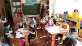 painting : ST. PETERSBURG, RUSSIA - CIRCA MAY, 2015: Woman educator begins lesson of painting with kids a pupils sitting at the desks. Russian kindergarten is a preschool educational institution