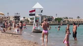 maritime territory : HURGHADA, EGYPT - CIRCA NOV, 2015: Lifeguard tower is on the full of people sandy beach in the Red Sea coastline. First line hotels area is on the Hurghada resort in Egypt