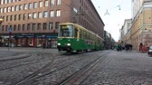 downtown : HELSINKI, FINLAND - CIRCA, DEC, 2015: Green streetcar drives on the Aleksanterinkatu street near the Senate Square in city. Public passenger ecological transport is in capital of Finland. Sound Stock Footage