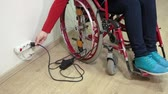 heavy : Woman with paralyzed legs sitting in wheelchair and stretching hard with plug to the power outlet
