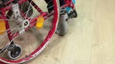 severely : Wheel of wheelchair with sitting disabled man turning on the parquet floor